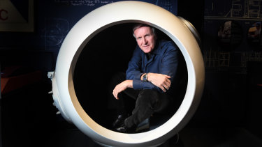 James Cameron poses for a photo with a scale model of the Deepsea Challenger cockpit at the media preview of the Challenging the Deep Exhibition at the Australian National Maritime Museum in Sydney.