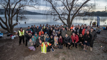 Participants in the winter solstice swim on the shores of Lake Burley Griffin, before they stripped off to swim nude for charity.
