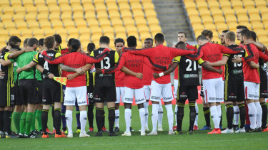 Respects: Phoenix and Wanderers players share a minute's silence for those killed in Friday's terror attack.