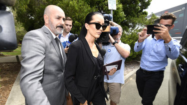 Basic (centre) is escorted to a limousine following her sentencing for drink driving.