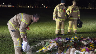Firefighters clean graffiti at the memorial for Eurydice Dixon.