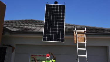 Going up: The Narang family get their solar panels installed by More Green Energy on their home in The Ponds, in Sydney's west, this week.