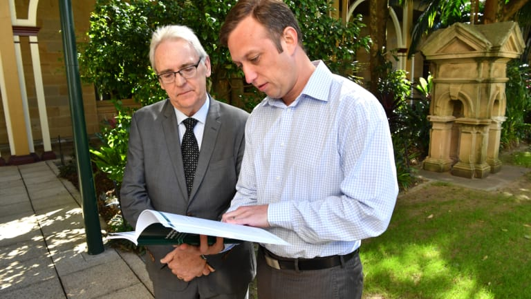 Former District Court judge Michael Forde (left) hands a report into Queensland's towing industry to then-acting minister for Main Roads Steven Miles (right) in August 2017.