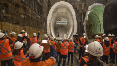 Workers watch the breakthrough of a giant tunnel boring machine at Crows Nest.