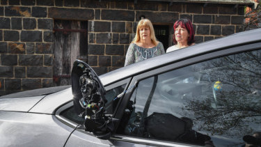 Julie Dougherty, 60, (left) and Leigh Mahady, 62, (right) stand next to the damaged car.
