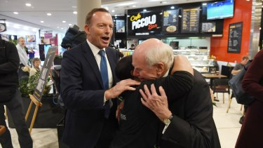 John Howard meets shoppers flanked by Tony Abbott.
