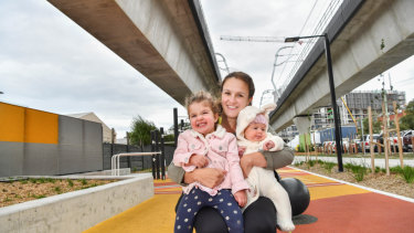 Dianne Liddell and her daughters Lillie Liddell, 2, and Florence Liddell, 4 months, under 'sky rail' in Carnegie.