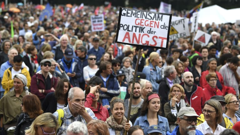 A woman with a poster reading 'United Against The Politics Of Fear' at a demonstration in Munich in July.