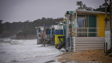 Beach boxes exposed to the sea at Mount Martha North