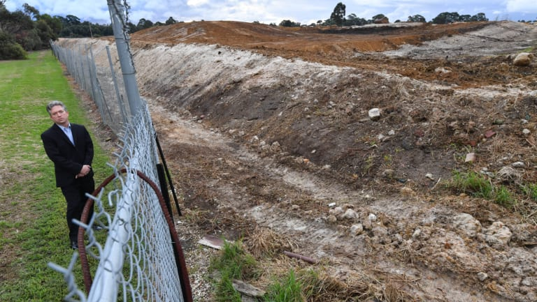 Curt Thompson stands at the boundary of a former quarry and rubbish dump in Oakleigh south.