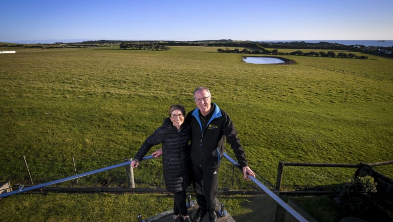 Land owners Karen Green and Robert Newall and, in the background, the farmland Matthew Guy briefly rezoned for housing.
