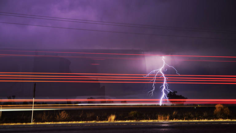 The silhouette of a semi trailer flickers past as lightning strikes the region north of Gunnedah as storms finally start to bring rain to some areas of northern NSW.