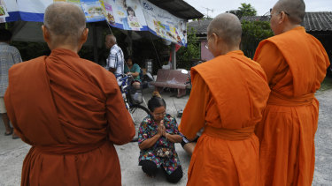 A woman kneels as she receives a blessing from female Theravada Buddhist monks.