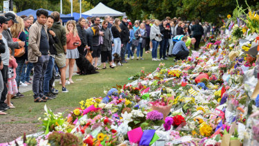 Aftermath: members of the public at a makeshift memorial in the Botanical Gardens in Christchurch.