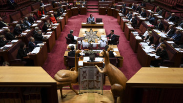 The emu and the kangaroo of the Australian coat of arms look down on the Senate chamber during Question Time.