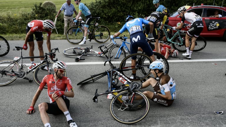 France's Axel Domont, right, and Poland's Tomasz Marczynski, left, grimace after crashing in the pack in the last kilometers during the fourth stage of the Tour de France.