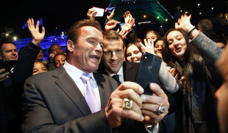 Arnold Schwarzenegger takes a selfie with French President Emmanuel Macron.