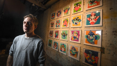 Al with the colourful collages on which he bases his paintings. All are for sale.