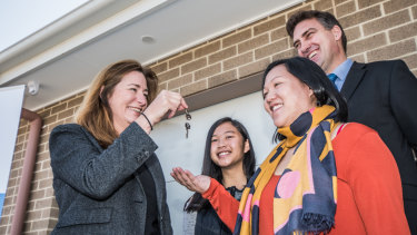 ACT Housing Minister Yvette Berry hands over the first keys to Christine Van and daughter Chloe ,15.