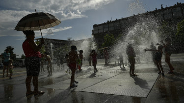 People cool off in a fountain in Pamplona, Spain.