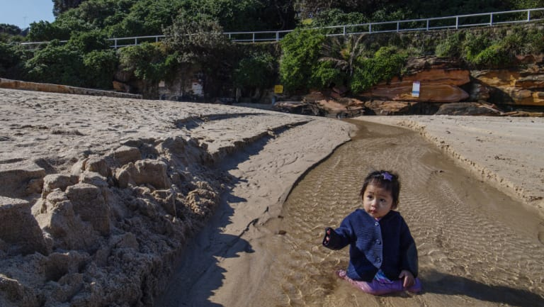 Anthem Mai, 1, playing where the storm water drain runs onto the north end of Coogee Beach.