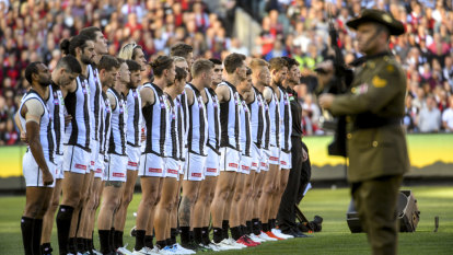 Collingwood players line up for the pre-game ceremony.