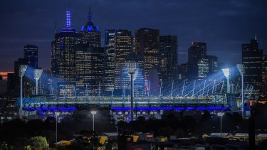 The MCG and city buildings turn blue in tribute to the four police officers who died on the Eastern Freeway a year ago today.