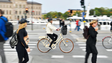 Commuters cycle through in Stockholm, Sweden, where COVID-19 cases have begun to rise again.
