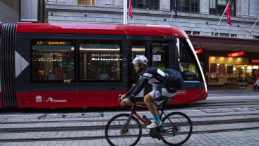 Cyclist in the CBD, George street, light rail, buses, generic workers. Coronavirus COVID-19 pandemic. 19th May 2020 Photo Louise Kennerley