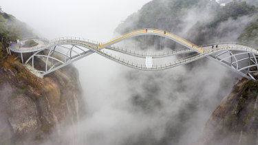Walkers brave the wavy, partially  glass-bottomed, 140-metre-high Ruyi Bridge in China's Zhejiang province.