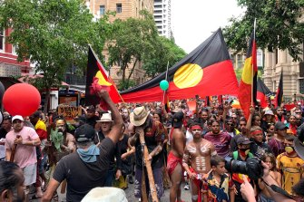 The Invasion Day protest moves through the Brisbane CBD last year.