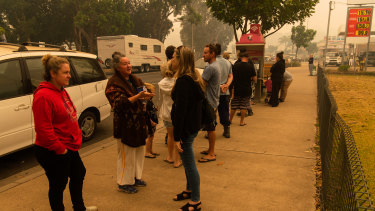 People lined up to use the public telephone in Narooma as power and telecommunications were down on New Year's Day.