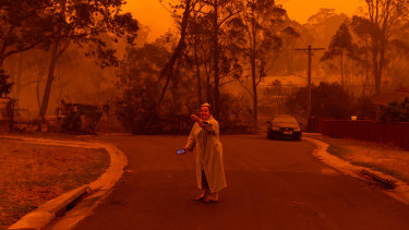 A resident of Mogo, on the NSW South Coast, outside her neighbours' property after fire engulfed the town.