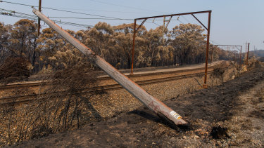 A burnt power pole fallen across the rails along the Blue Mountains Line,  near Dargan.