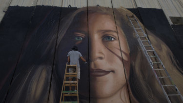 An artist paints a giant mural of prominent Palestinian activist Ahed Tamimi on part of the Israeli separation wall, in the West Bank city of Bethlehem on  July 25.