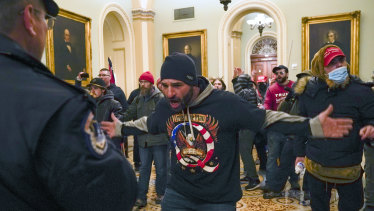 Trump supporters confront US Capitol Police in the hallway outside of the Senate chamber at the Capitol in Washington.