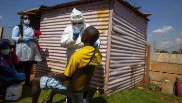 Health workers collects samples for coronavirus testing outside a shack to combat the spread of COVID-19 at Lenasia South, Johannesburg, South Africa.