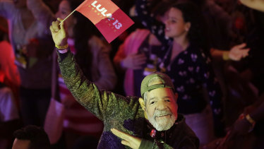 A man wears a mask depicting the Brazil's former President Luiz Inacio Lula da Silva during a Workers Party national convention in Sao Paulo, Brazil, on Saturday.