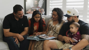 Keith's dad Paul, sister Zara, mother Lafo, brother Jesse and nephew Hudson looking at family photo albums as they remember the life of their loved one.