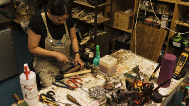 A cobbler handmakes a pair of boots that will be worn in Hamilton.