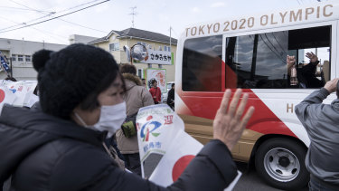 A woman waves to a bus transporting Japanese comedy duo Sandwich Man holding the Olympic flame after the Tokyo 2020 Olympic Games torch arrival ceremony in Matsushima on March 20.