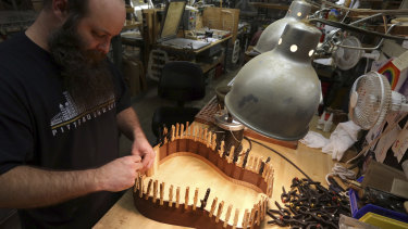 A luthier assembles the rosewood sides of a guitar at C. F. Martin and Co. guitar makers.