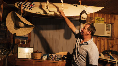 Dave Pearson, with the surfboard on which he was attacked.