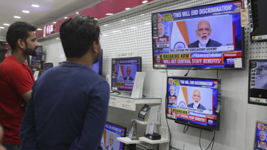 Indians watch Prime Minister Narendra Modi address the nation.