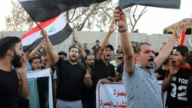 Demonstrators wave national flags and chant slogans during a demonstration demanding better public services in Basra on Tuesday.