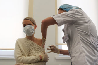 A health worker injects the 'Gam-COVID-Vac', also known as 'Sputnik V', COVID-19 vaccine, into a patient's arm in Moscow, Russia, on Saturday.