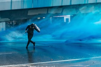 Pro-democracy protesters react as police fire water cannons at them outside the Central Government Complex on September 15, 2019 in Hong Kong.