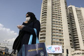 A pedestrian wearing a face mask crosses a street in northern Tehran.