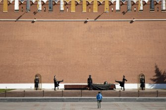 A man watches as the Kremlin guards change at the Tomb of Unknown Soldier in almost empty Alexander's Garden at the Kremlin Wall in Moscow, on state holiday, May 1.