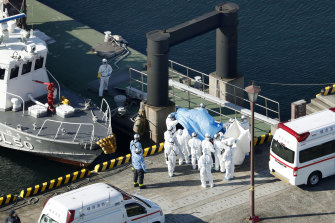 Medical workers in protective suits lead a passenger tested positive for a new coronavirus from the cruise ship Diamond Princess at Yokohama.